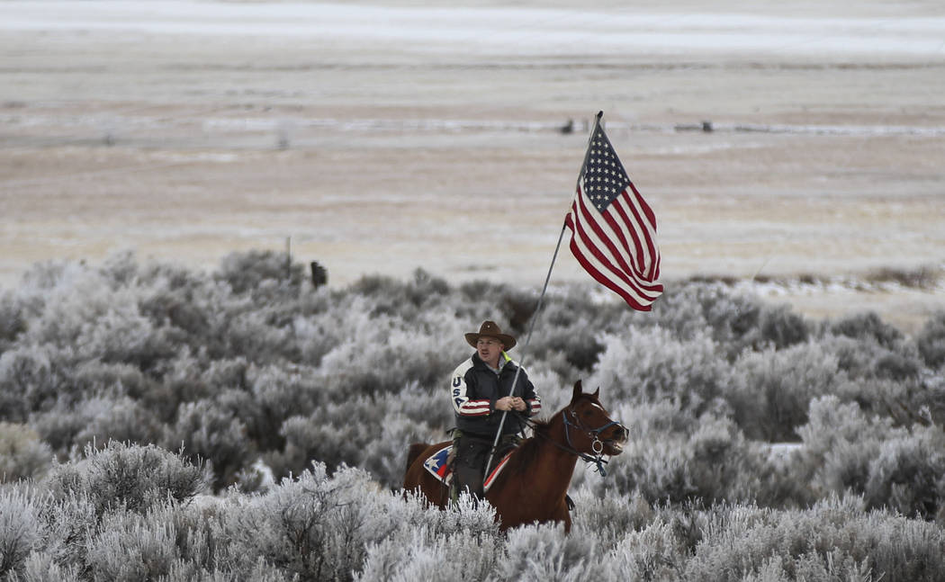 Anti-government protester Duane Ehmer of Irrigon, Ore. rides his horse, Hellboy, near the entrance of the Malheur National Wildlife Refuge headquarters, which the group is occupying, near Burns, O ...