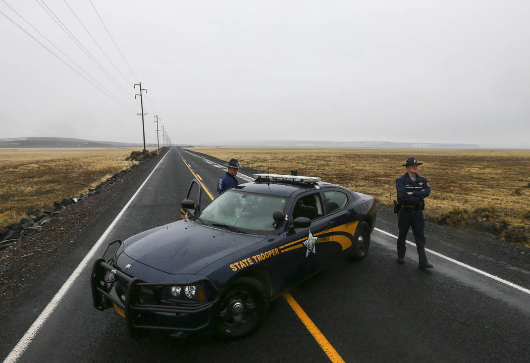 Oregon State Police block the road outside of the Malheur National Wildlife Refuge, where four anti-government protesters remain, about 30 miles south of Burns, Ore., on Thursday, Jan. 28, 2016. T ...
