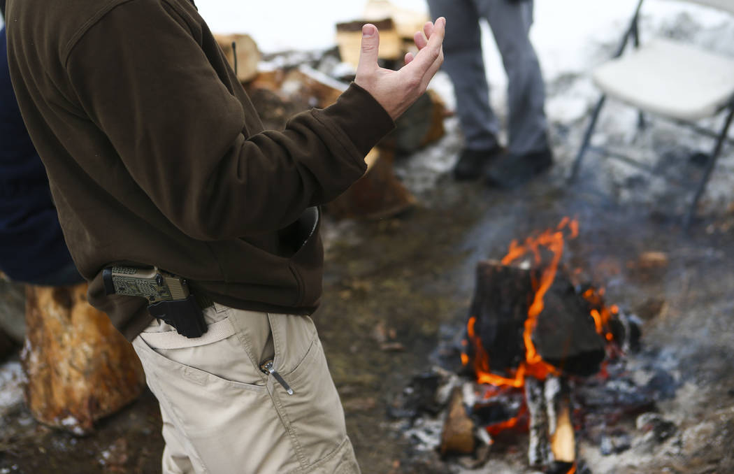 Anti-government protester Jon Ritzheimer talks by a fire while guarding the entrance of the Malheur National Wildlife Refuge headquarters, which the group is occupying, near Burns, Ore. on Thursda ...