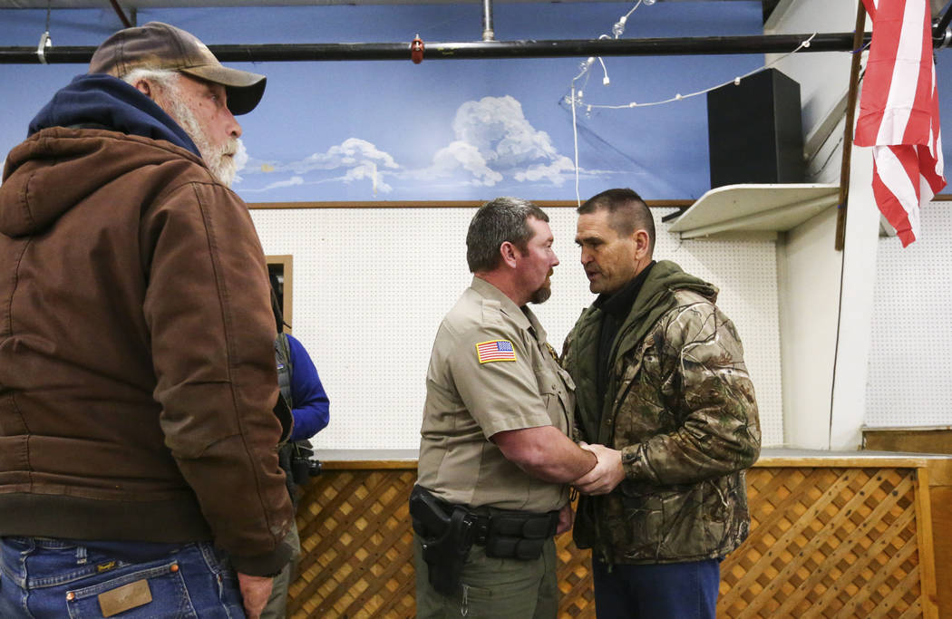 Alan Johnson, right, greets Harney County Sheriff Dave Ward during a community meeting to address concerns in Burns, Ore. on Wednesday, Jan. 6, 2016. Anti-government protestors have taken over the ...