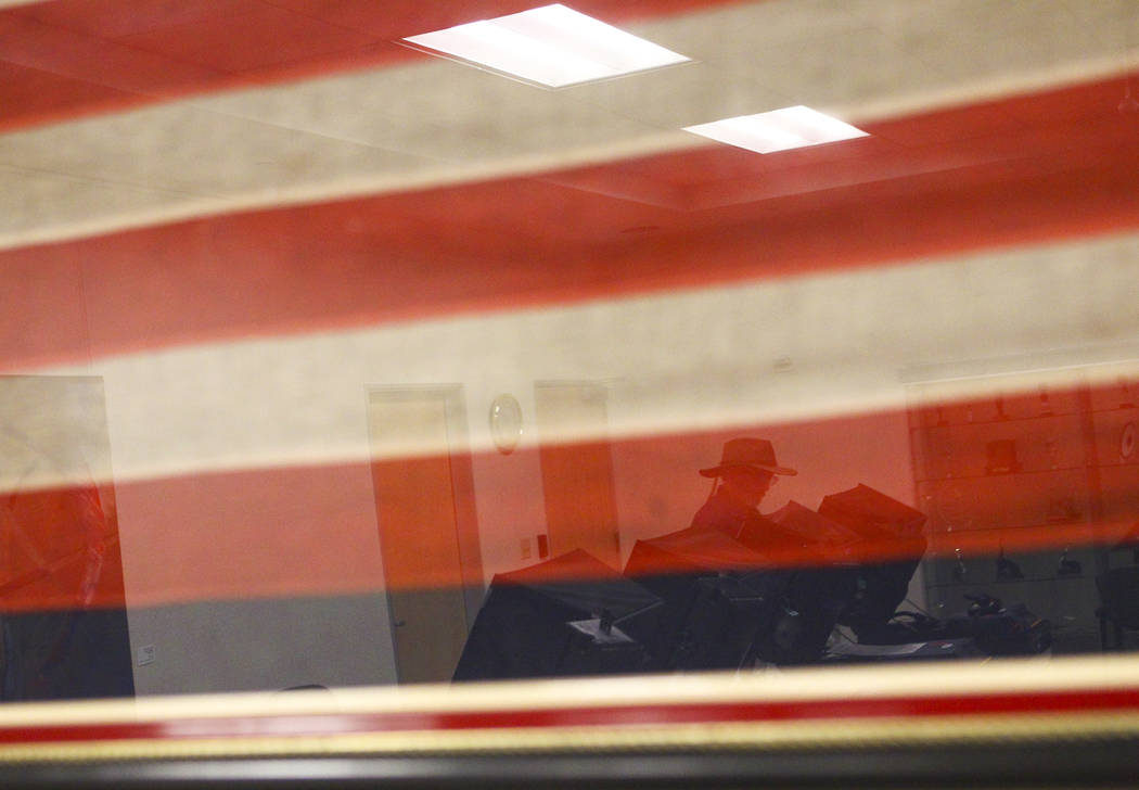 Chris Lang, reflected in a glass from holding the first honor flag to be flown over the city of Las Vegas, votes early ahead of the Las Vegas municipal election at Las Vegas City Hall on Tuesday,  ...