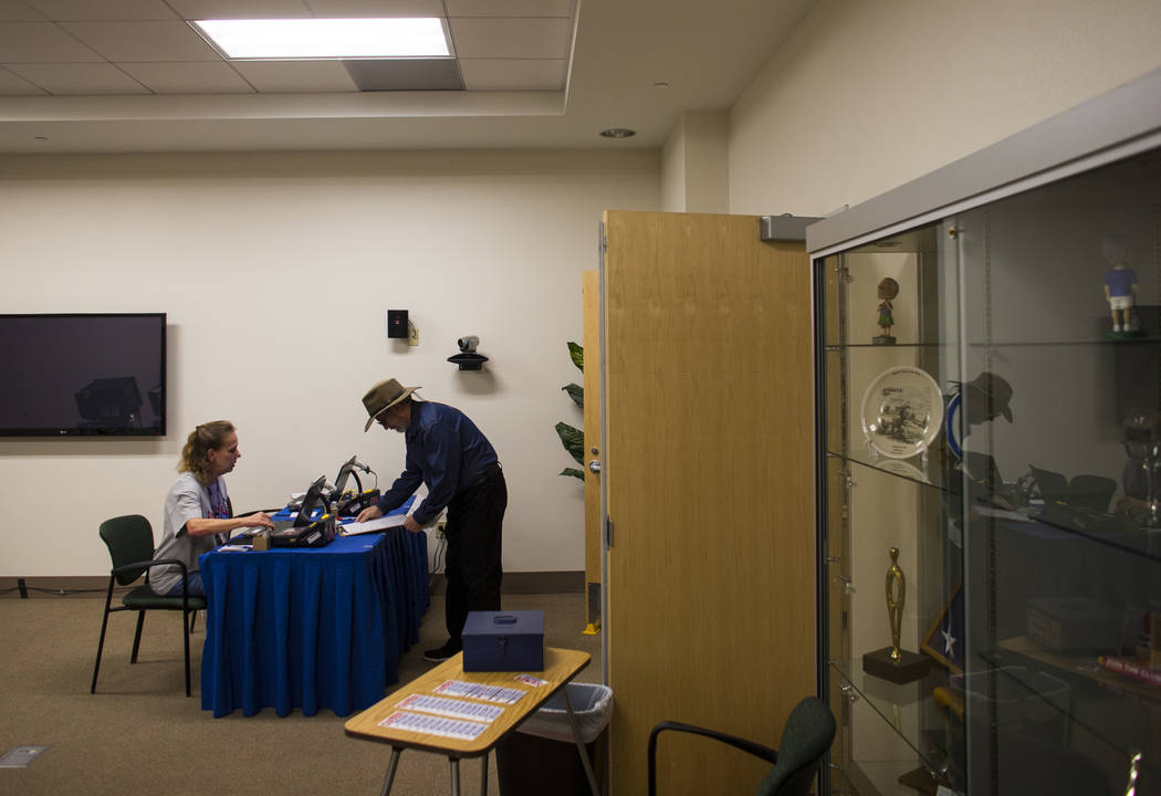 Kelly DiNicola, left, checks in Chris Lang to vote early ahead of the Las Vegas municipal election at Las Vegas City Hall on Tuesday, March 28, 2017. (Chase Stevens/Las Vegas Review-Journal) @csst ...