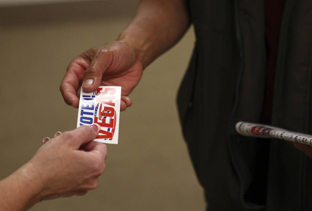 """Samban Samuel Khin, a first time voter, receives an """"I Voted"""" sticker after eating his ballot early ahead of the Las Vegas municipal election at Las Vegas City Hall on Tuesday, M ..."""