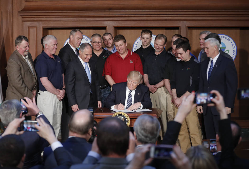 President Donald Trump, accompanied by Environmental Protection Agency Administrator Scott Pruitt, third from left, and Vice President Mike Pence, right, signs an Energy Independence Executive Ord ...