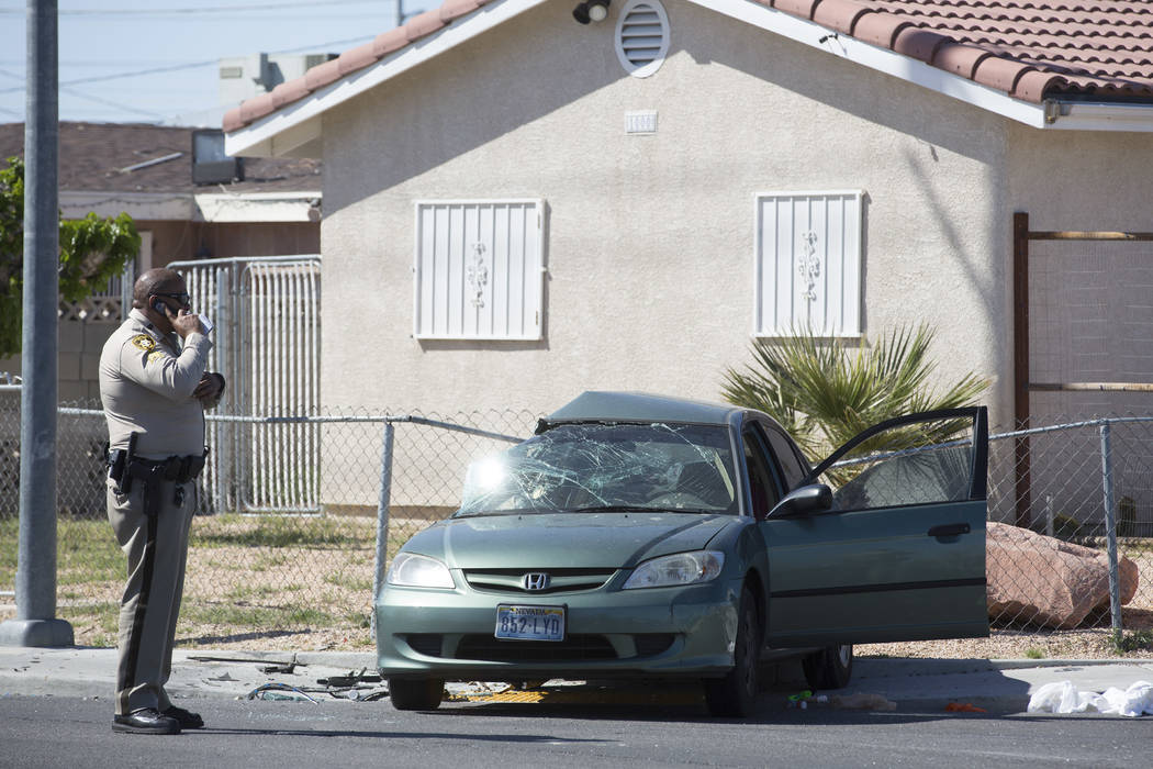 An officer surveys the damages of an accident near the intersection of I Street and Washington Avenue on Tuesday, March 28, 2017, in Las Vegas. A juvenile was transported to UMC. (Bridget Bennett/ ...