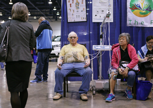 Lloyd Probasco, center, and Becky Shui, right, participate in electrical stimulation therapy at the Neuropathy and Pain Centers of America booth during the Successful Aging Expo at Cashman Center  ...