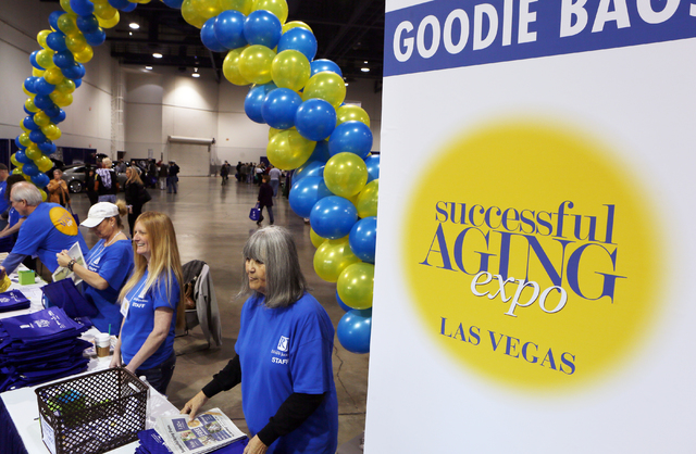 Workers pass out programs and bags at the entrance to the Successful Aging Expo at Cashman Center Saturday, Jan. 31, 2015, in Las Vegas. The one-day expo offers free seminars and exhibits that pro ...