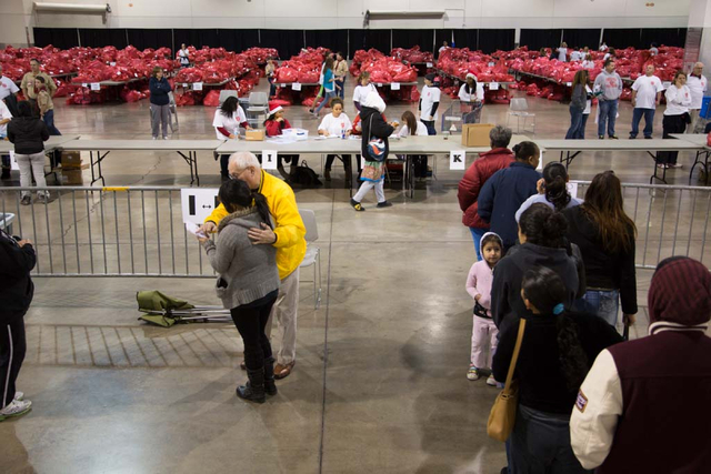 Recipients wait for their turn to receive their toys and gift cards from Salvation Army volunteers at the Cashman Center in Las Vegas on Saturday, Dec. 21, 2013. Down from last years' ability to p ...