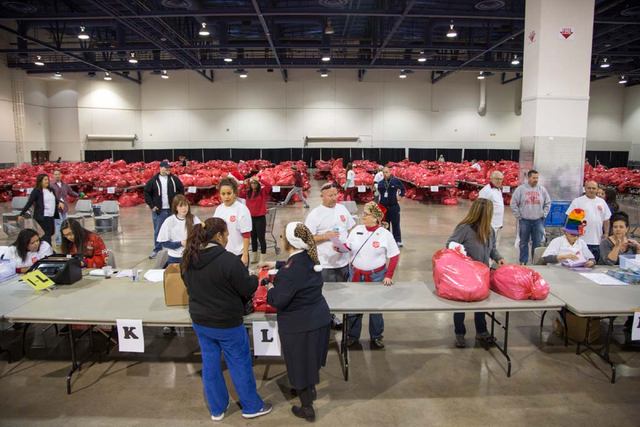 Salvation Army volunteers deliver bags of toys to recipients at the Cashman Center in Las Vegas on Saturday, Dec. 21, 2013. Down from last years' ability to provide gifts to 9,000, The Salvation A ...