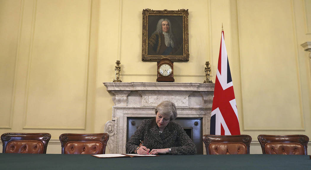 Britain's Prime Minister Theresa May, sitting below a painting of Britain's first Prime Minister Robert Walpole, signs the official letter to European Council President Donald Tusk, in 10 Downing  ...