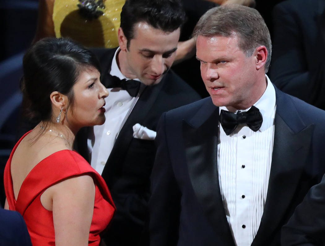 "Brian Cullinan, right, and Martha Ruiz of PricewaterhouseCoopers confer on stage after the Academy Award's Best Picture was mistakenly awarded to ""La La Land"" instead of ""Moonlight."" (Lucy Nichols ..."