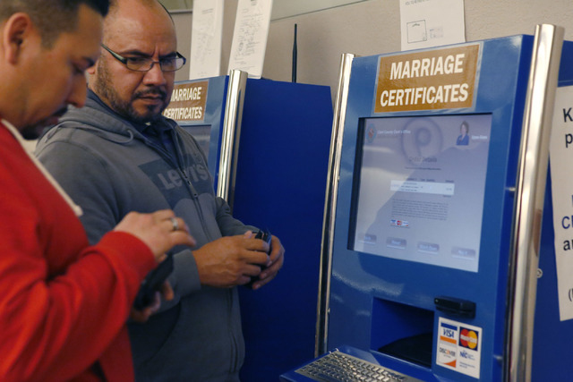 Raul Luna, 37, left, and Luis Zamarripa, 49,  right, purchase their marriage certificate at the Clark County Marriage License Bureau on Tuesday, Feb. 21, 2017, in Las Vegas. (Christian K. Lee/Las  ...