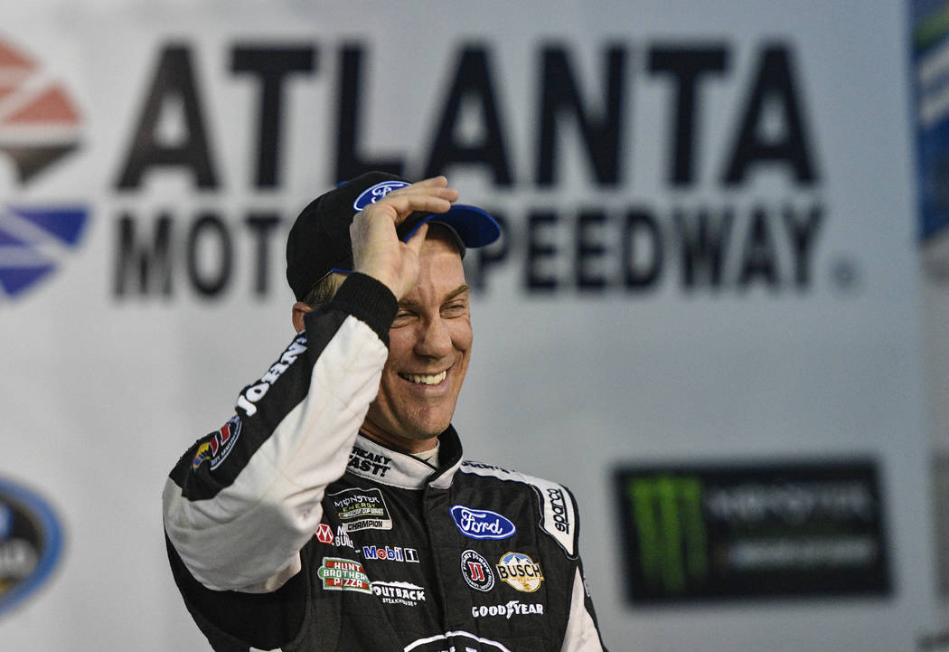 Kevin Harvick stands in Victory Lane after winning the pole for the NASCAR Monster Energy Cup auto race at Atlanta Motor Speedway in Hampton, Ga., Friday, March 3, 2017. (AP Photo/John Amis)