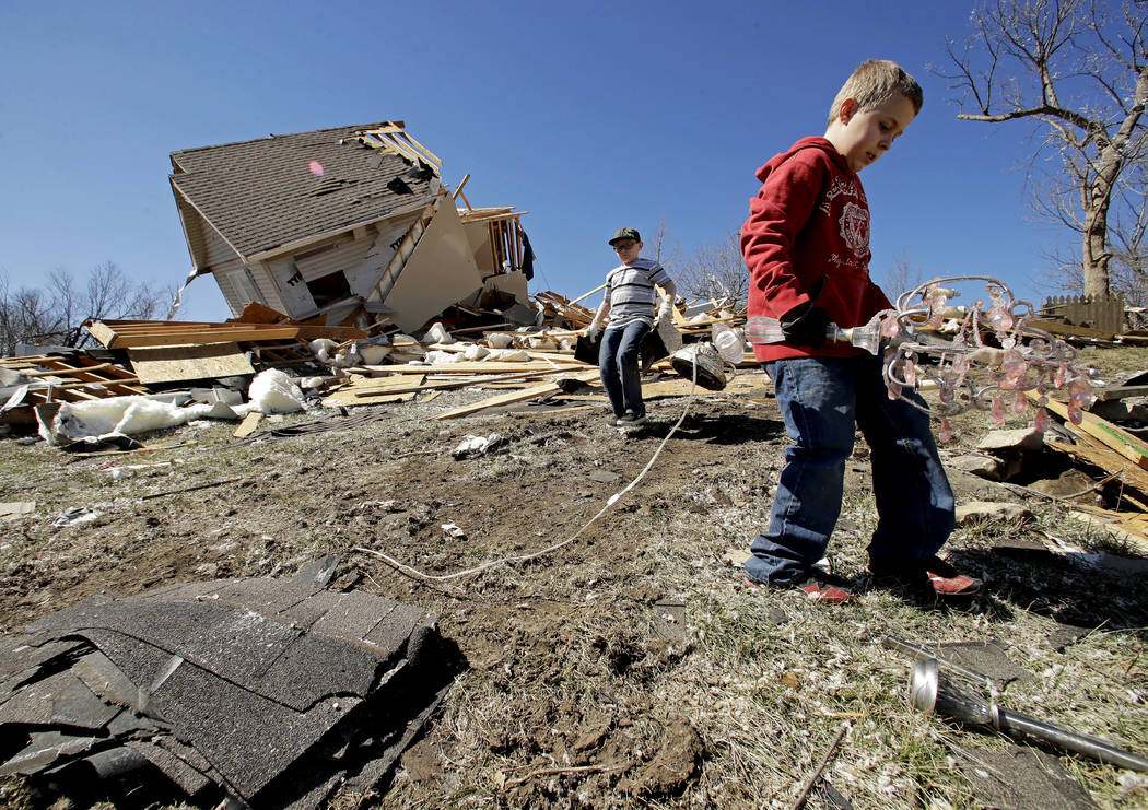 Kadin Lance, right, and his brother Carter Lance pick up debris at a friend's destroyed home Tuesday, March 7, 2017, after a tornado damaged tore through Oak Grove, Mo., Monday night. Charlie Ried ...