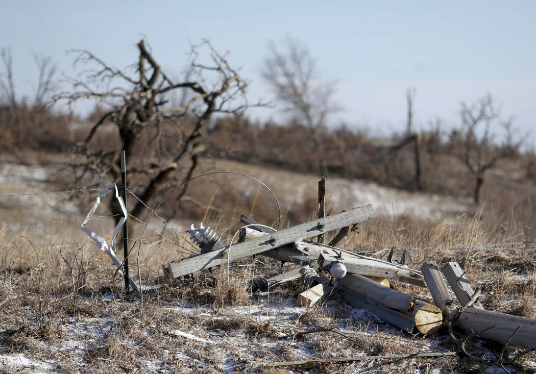 A downed power pole from a storm Monday evening is scattered on the ground, Tuesday, March 7, 2017, in Orrock Township near Zimmerman, Minn.  Weather experts say a likely tornado touched down nort ...