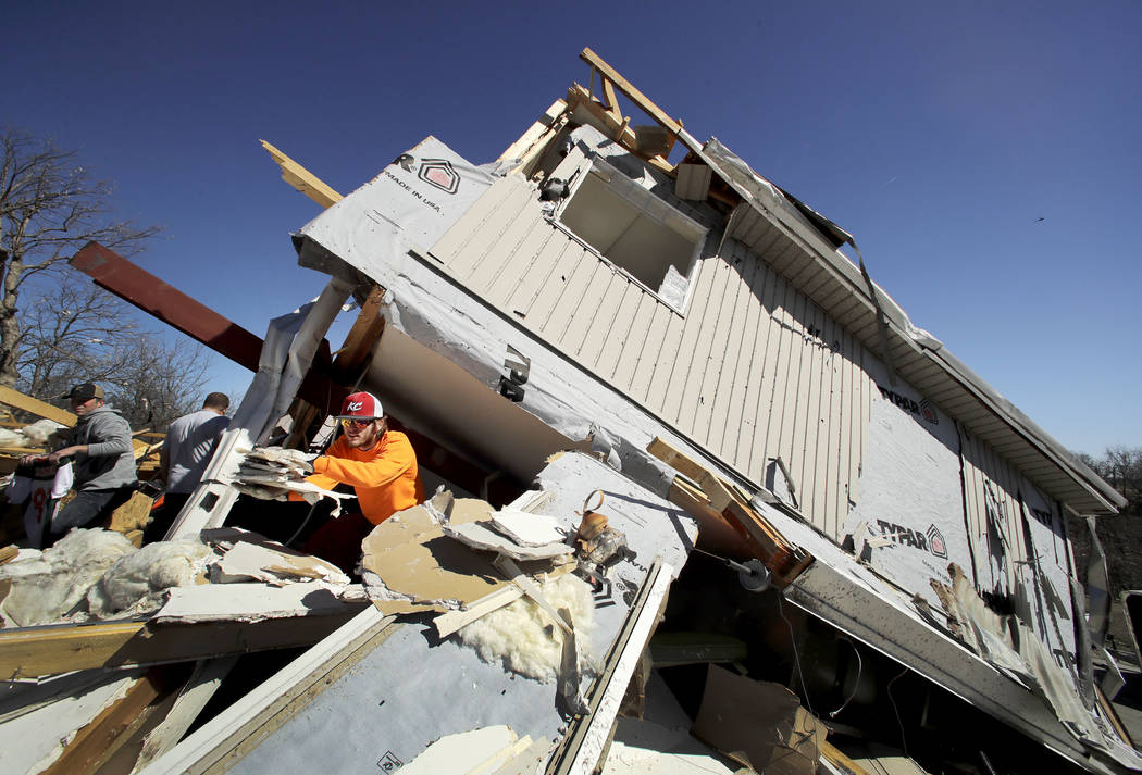 Skyler Jackson salvages items from a friend's destroyed home Tuesday, March 7, 2017, after a tornado tore through Oak Grove, Mo., Monday night. (Charlie Riedel/AP)
