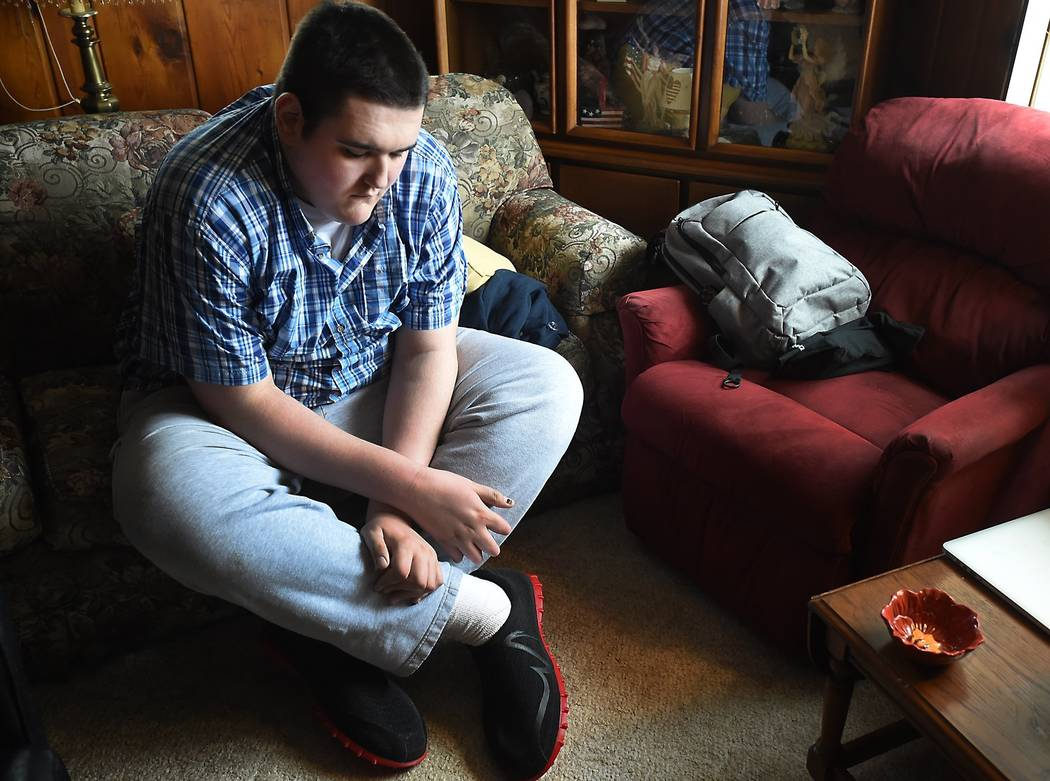 Broc Brown checks out his new shoes at his grandmother's home in Michigan Center, Mich. Brown, who has Sotos Syndrome and is 7 feet, 8 inches tall, was given a new pair of about size 28 shoes from ...