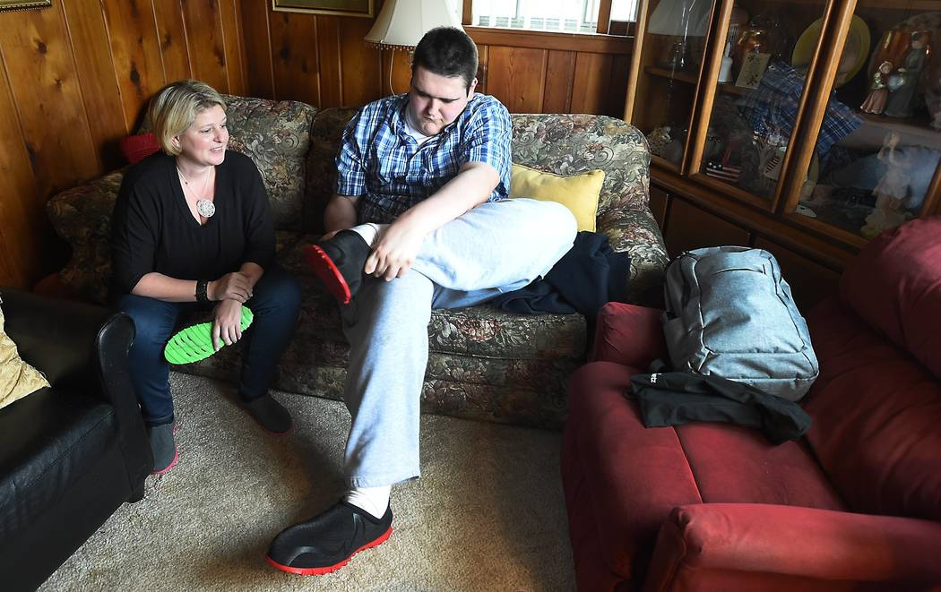 Broc Brown puts on his new shoes as Feetz CEO Lucy Beard watches at his grandmother's home in Michigan Center, Mich.  Brown, who has Sotos Syndrome and is 7 feet, 8 inches tall, was given a new pa ...