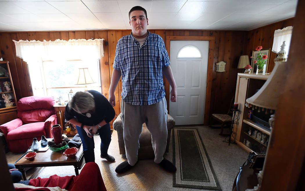 Broc Brown stands up in his new shoes as Feetz CEO Lucy Beard checks the fit at his grandmother's home in Michigan Center on Wednesday, March 1, 2017. Brown, who has Sotos Syndrome and is 7 feet,  ...