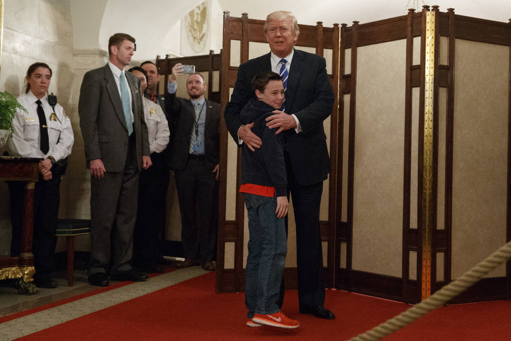 President Donald Trump hugs Jack Cornish, 10, of Birmingham, Ala. as he greets visitors touring the White House in Washington, Tuesday, March 7, 2017. (Evan Vucci/AP)