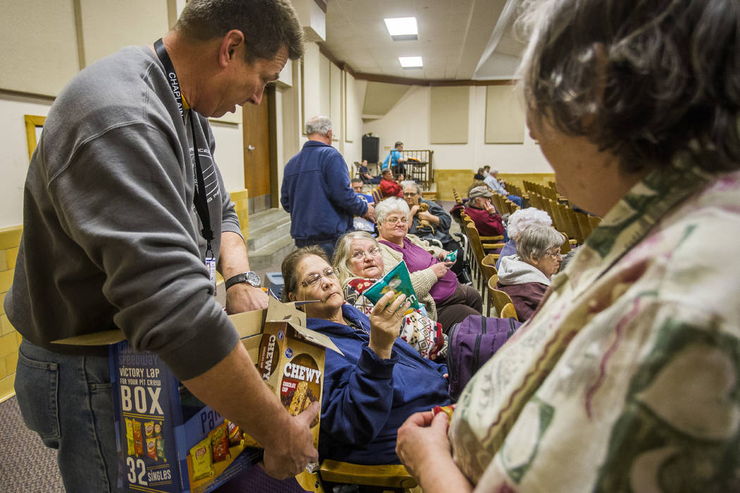 Southern Baptist Disaster Relief Chaplain Jeff Thompson passes bags of chips to, from left to right, Suzanne Morgan, Carol Shaylor and Linda Nimmo Monday, March 6, 2017, inside an evacuation cente ...