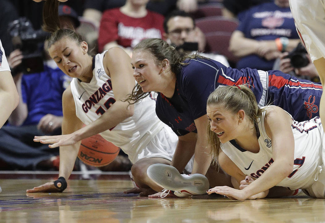 From right, Gonzaga's Laura Stockton, Saint Mary's Sydney Raggio and Gonzaga's Jill Barta scramble for the ball in the first half of an NCAA college basketball game during the championship of the  ...