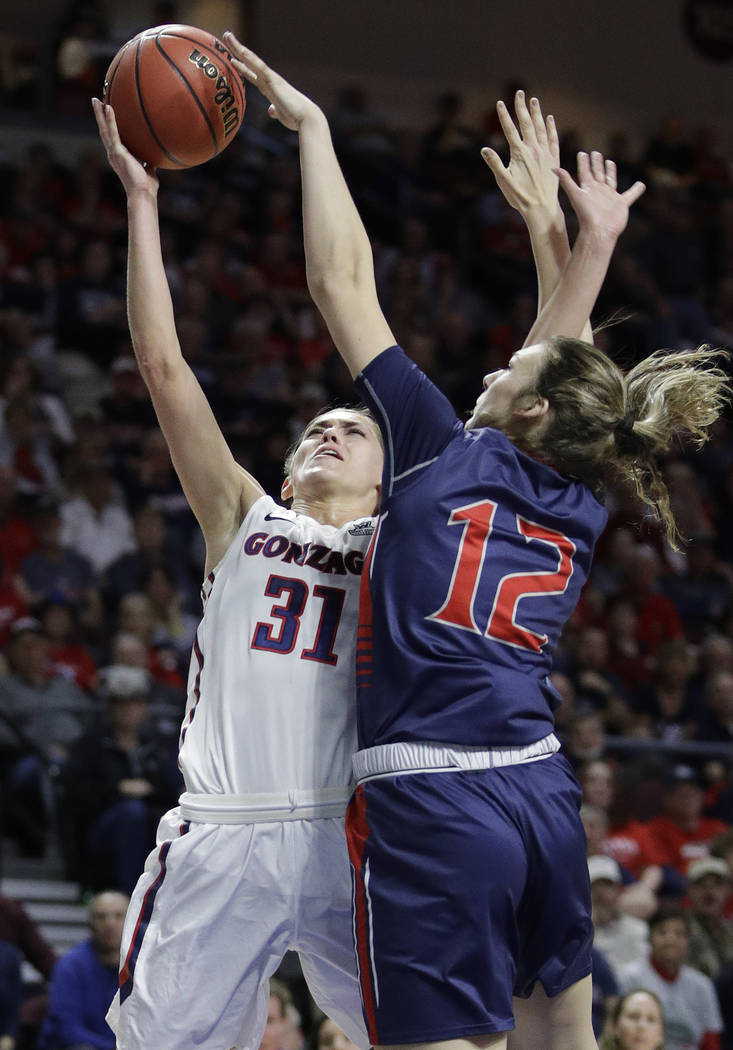 Gonzaga's Elle Tinkle, left, shoots over Saint Mary's Sydney Raggio in the first half of an NCAA college basketball game in the championship of the West Coast Conference tournament, Tuesday, March ...