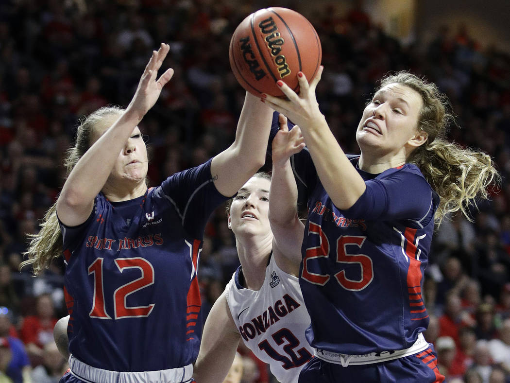 Saint Mary's Sydney Raggio, left, and Megan McKay, right, go for a rebound against Gonzaga's center Emma Wolfram (12) in the first half of an NCAA college basketball game during the championship o ...
