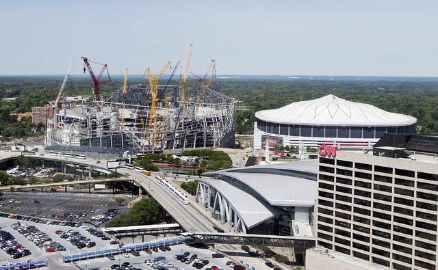 Mercedes-Benz Stadium, the future home of the Atlanta Falcons football team stands under construction, at left, next to the team's current stadium, the Georgia Dome, Monday, May 16, 2016, in Atlan ...