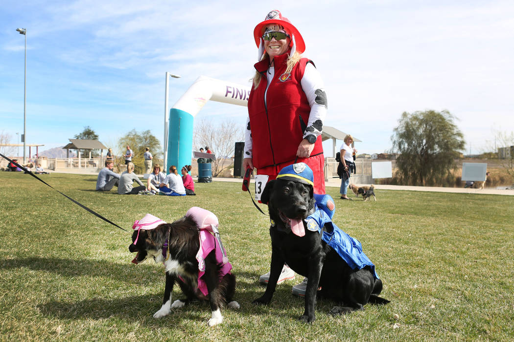 Erika Balderson, a competitor in the Rover Run 5K, with her dogs Tere, a border collie mix, left, and Tai, a black Labrador, during the Bark In the Park, an event to celebrate dogs, at Cornerstone ...