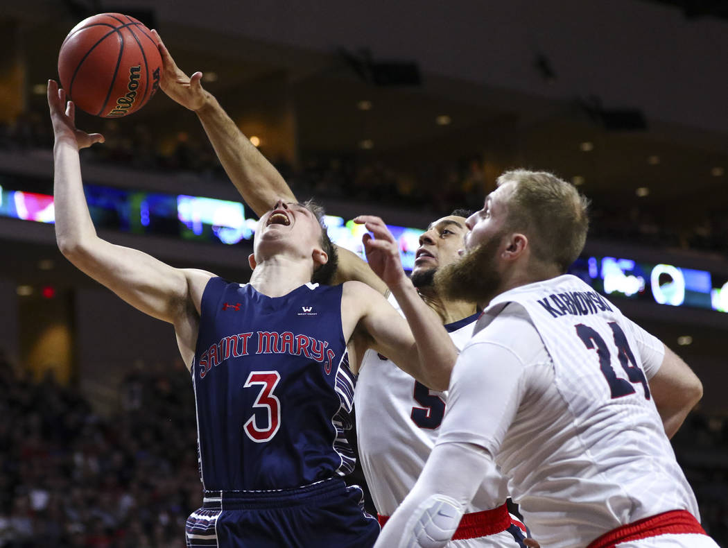 Gonzaga guard Nigel Williams-Goss (5) blocks a shot from St. Mary's guard Emmett Naar (3) as Gonzaga center Przemek Karnowski (24) looks on during the West Coast Conference basketball championship ...