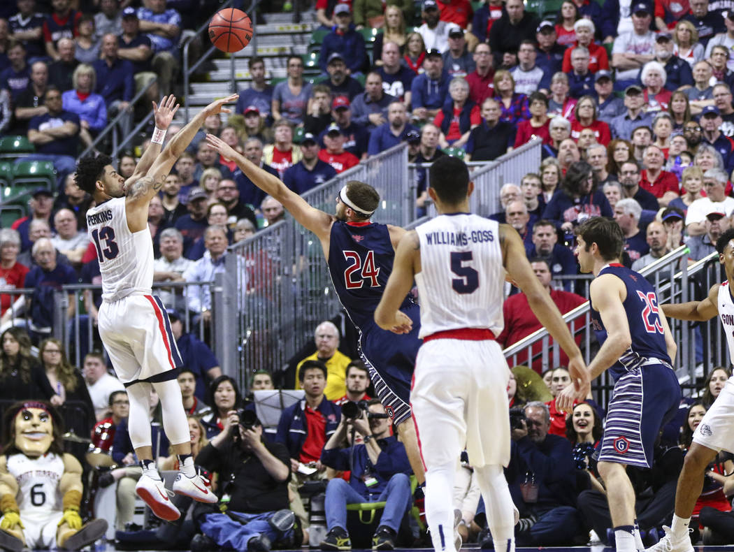 Gonzaga guard Josh Perkins (13) shoots to score a three-pointer over St. Mary's forward Calvin Hermanson (24) during the West Coast Conference basketball championship game at the Orleans Arena in  ...
