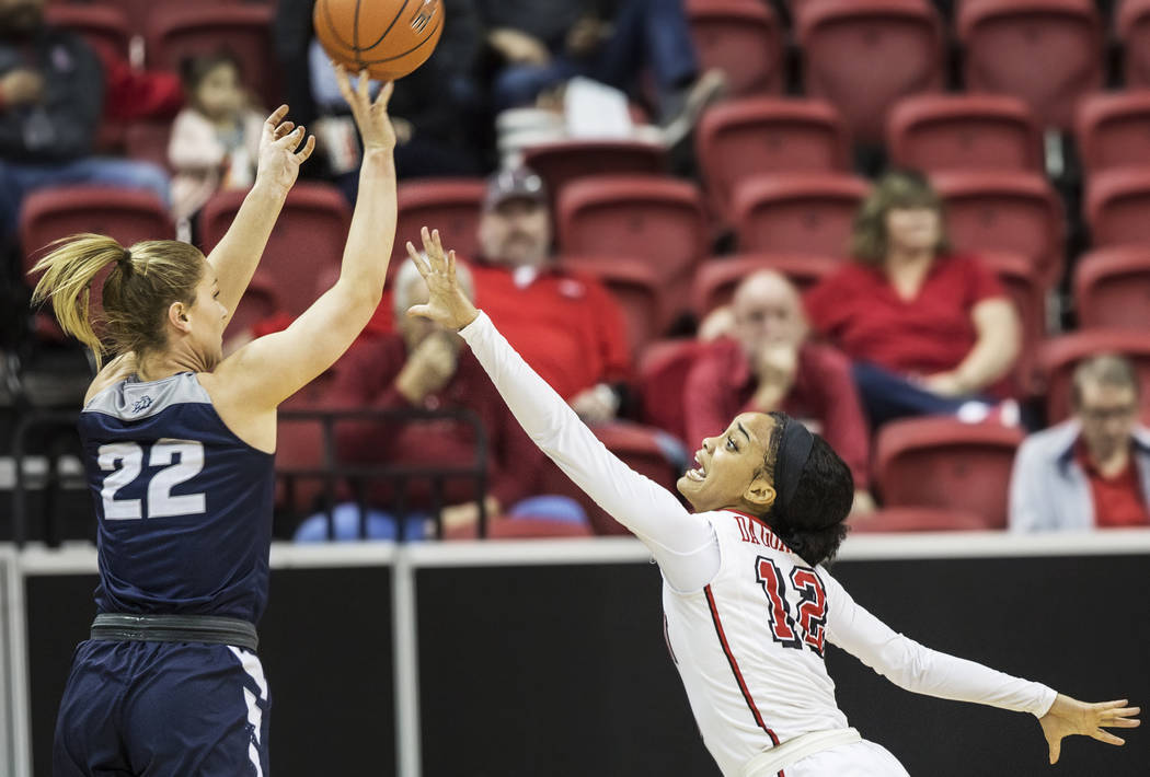 UNLV's Dakota Gonzalez (12) reaches out to block the shot of Utah State's Rachel Brewster (22) during the second round of the Mountain West tournament on Tuesday, March 7, 2017, at Thomas & Ma ...