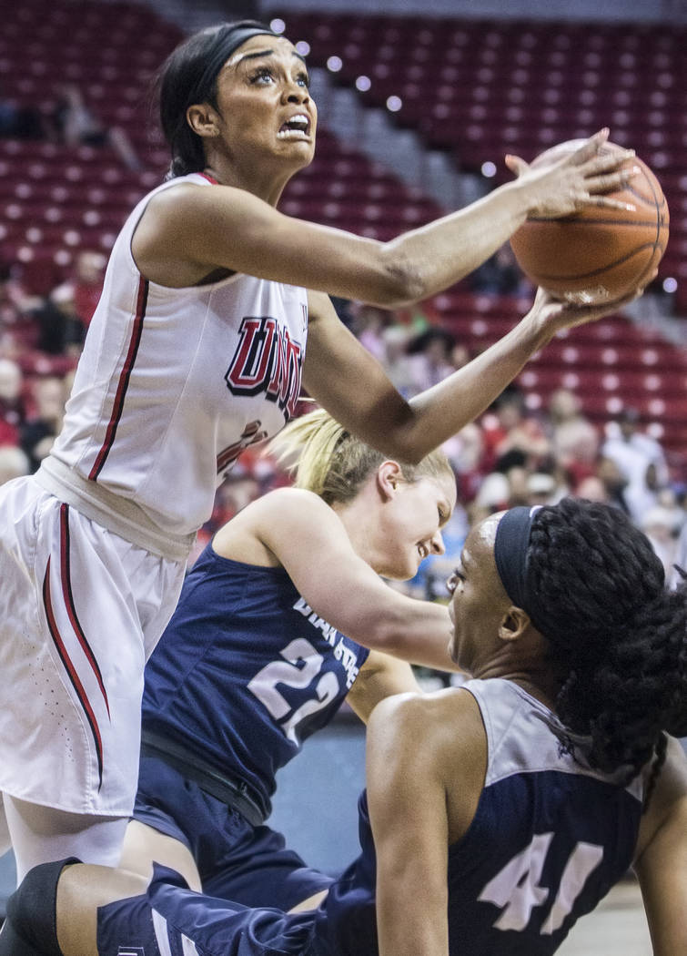 UNLV's Dakota Gonzalez (12) collides with Utah State's Antoina Robinsonson (41) and Rachel Brewster (22) during the second round of the Mountain West tournament on Tuesday, March 7, 2017, at Thoma ...