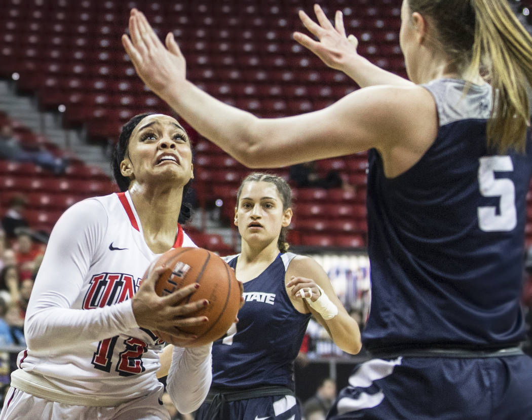 UNLV's Dakota Gonzalez (12) slices to the basket past Utah State's Shannon Dufficy (5) during the second round of the Mountain West tournament on Tuesday, March 7, 2017, at Thomas & Mack Cente ...