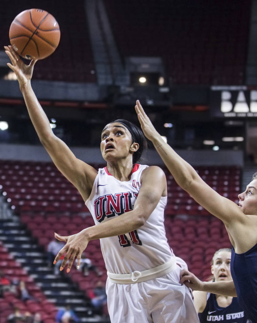 UNLV's Dylan Gonzalez (11) slices to the basket past Utah State's Rachel Brewster (22) during the second round of the Mountain West tournament on Tuesday, March 7, 2017, at Thomas & Mack Cente ...