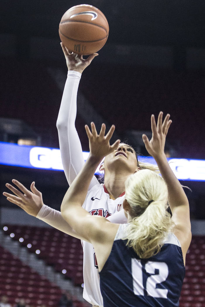 UNLV's Katie Powell (21) shoots a jump hook over Utah State's Hailey Bassett (12) during the second round of the Mountain West tournament on Tuesday, March 7, 2017, at Thomas & Mack Center, in ...