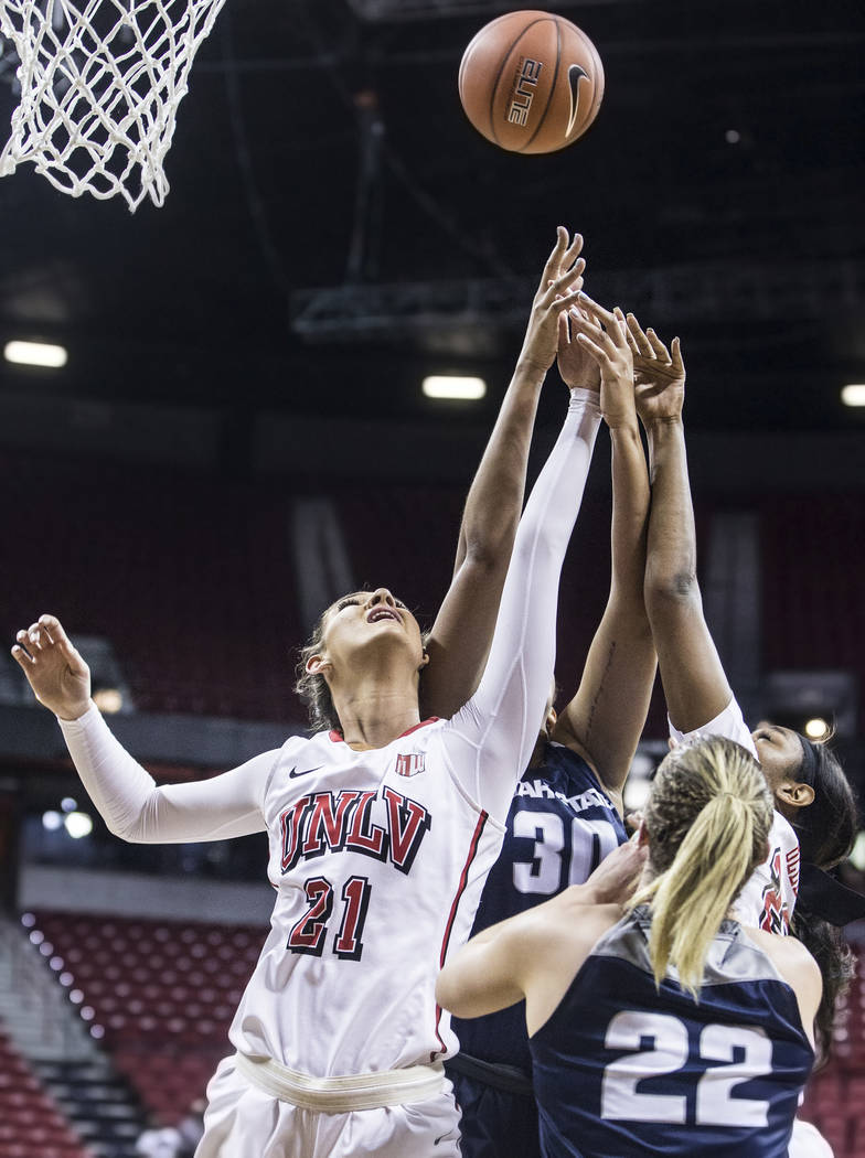 UNLV's Katie Powell (21) fights for a rebound with Utah State's Dee Moore (30) and Rachel Brewster (22)  during the second round of the Mountain West tournament on Tuesday, March 7, 2017, at Thoma ...