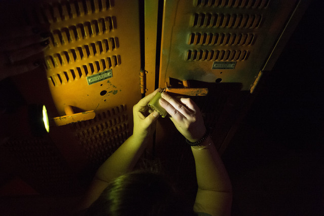 Participants at The Basement escape room try to unlock a locker using various codes in hope of getting one step closer to freedom. (Bridget Bennett/Las Vegas Review-Journal) @bridgetkb