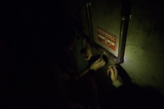 Participants follow a sign instructing water shut off in attempts to escape at The Basement Escape Room in Las Vegas. (Bridget Bennett/Las Vegas Review-Journal) @bridgetkb