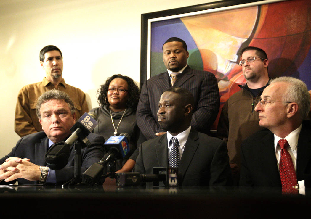 Victor Fakoya, center, becomes emotional at a press conference announcing a federal civil lawsuit against Clark County at the law offices of Ales & Bryson, LLP in Las Vegas on Tuesday, Dec. 18 ...