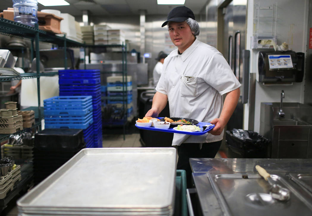 Connor Miranda, 19, carries a tray of food in the kitchen at the Heritage Park Senior Facility in Henderson on Thursday, March 2, 2017. (Brett Le Blanc/View) @bleblancphoto