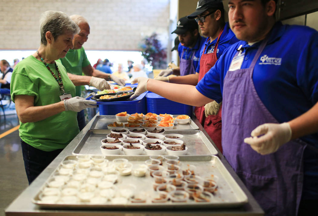 Volunteers take plates of food to deliver to tables during lunch at the Heritage Park Senior Facility in Henderson on Thursday, March 2, 2017. (Brett Le Blanc/View) @bleblancphoto