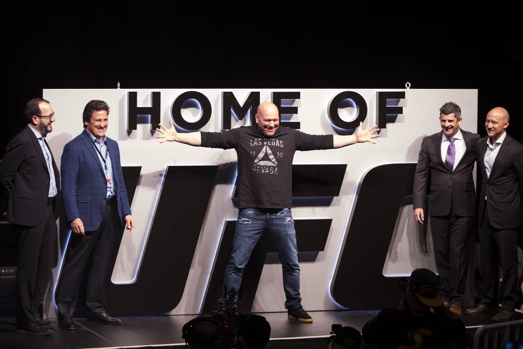 Ultimate Fighting Championship President Dana White, center, in front of a new sign revealed at T-Mobile Arena after UFC was announced as an anchor of the arena on Friday, March 3, 2017, in Las Ve ...