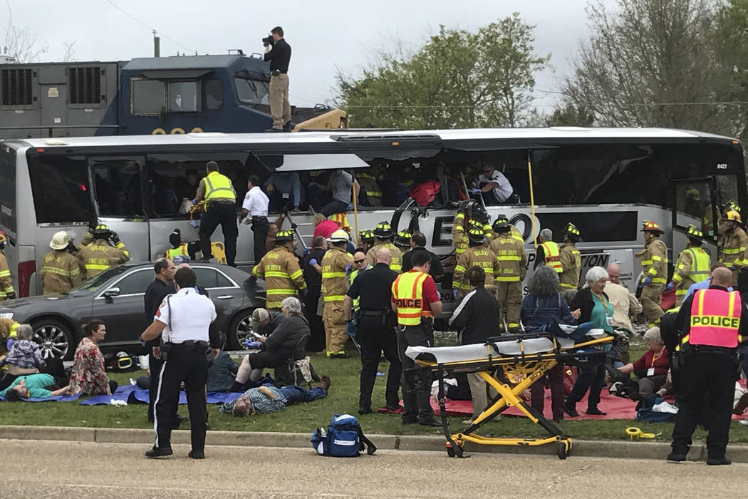 Biloxi, Miss., firefighters help passengers of a charter bus out of the damaged vehicle after the bus collided with a train Tuesday afternoon, March 7, 2017. (John Fitzhugh/The Sun Herald via AP)
