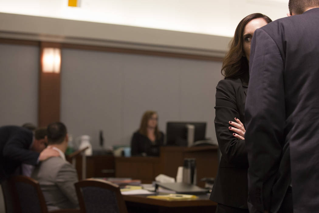 Prosecutors Jacqueline Bluth and Rob Stephens, in the foreground, speak while the defense gathers in the background after opening statements at the Regional Justice Center on Monday, March 6, 2017 ...