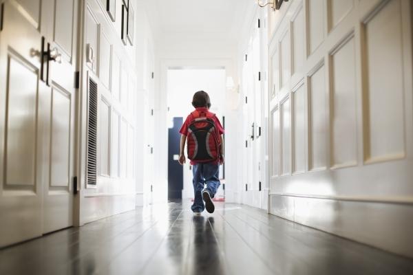 Boy Walking in Hallway Wearing Backpack
