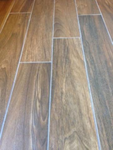 Courtesy of Sun West Custom Homes  Wood-look tile floors offer the durability of tile but the style of hardwood floors.