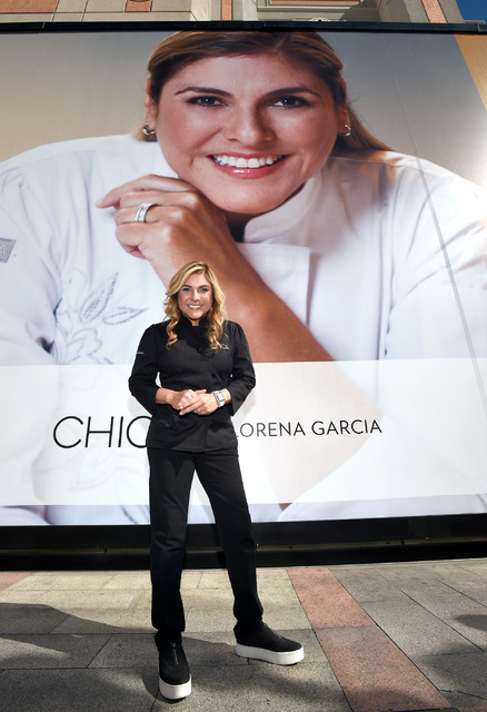 Chef Lorena Garcia poses by a 21-foot-tall poster of herself after its debut on the wall of chefs at the Venetian Las Vegas Wednesday, Feb. 15, 2017, in Las Vegas. David Becker Las Vegas News Bureau