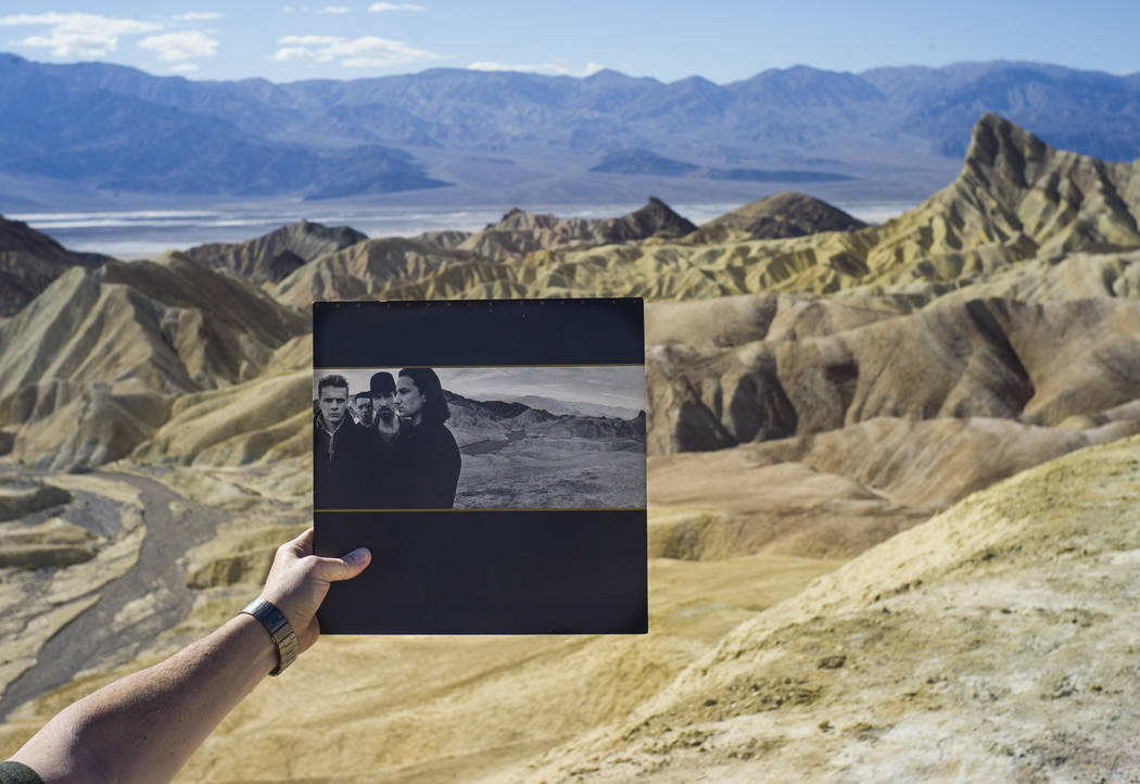 """Zabriskie Point, featured in the album artwork of U2's 1987 album """"The Joshua Tree,"""" is shown with a copy of the album in Death Valley National Park on Tuesday, Feb. 28, 2017. (C ..."""